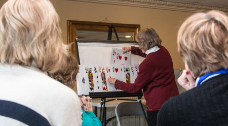 A woman using large playing cards on an easel.